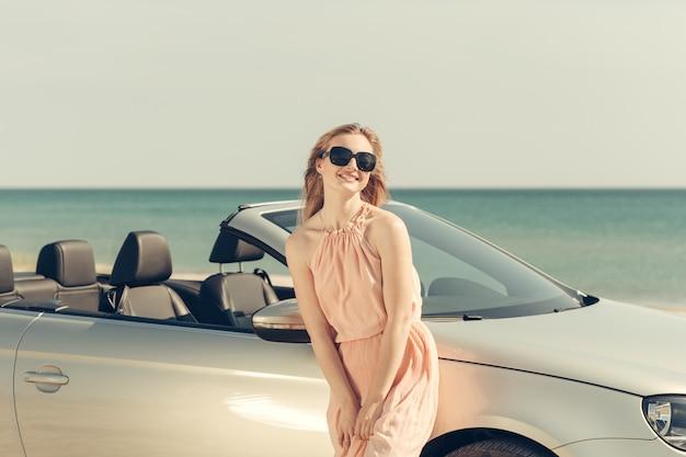 De jonge vrouw drijft een auto op het strand Premium Foto