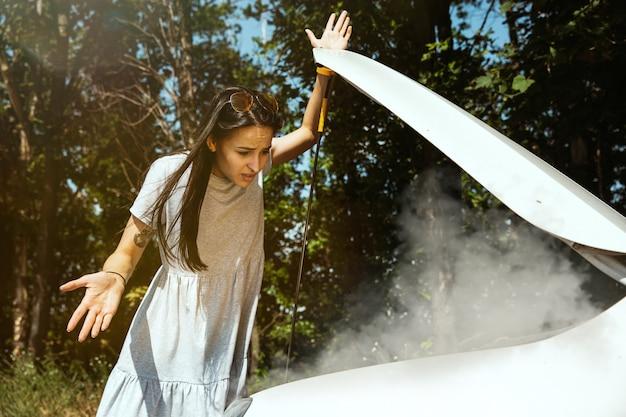 De jonge vrouw gaf de auto pech terwijl ze onderweg was om uit te rusten. ze probeert de kapotte zelf te repareren of zou moeten liften. nerveus worden. weekend, problemen onderweg, vakantie. Gratis Foto