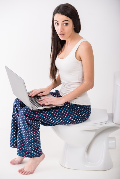 De jonge vrouw gebruikt laptop terwijl in een toilet zit. Premium Foto