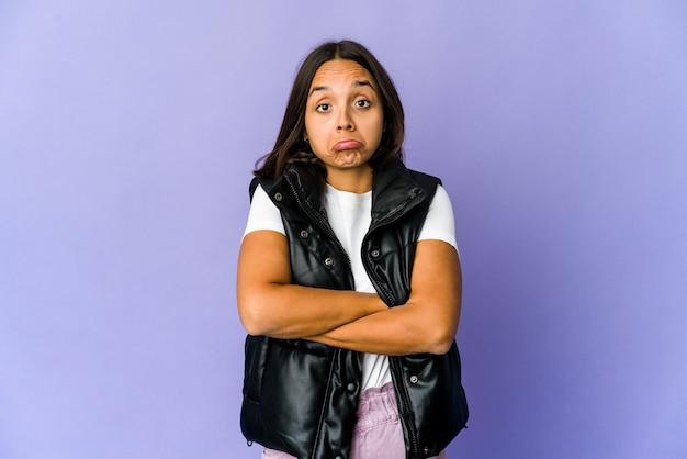 De jonge vrouw haalt schouders op en opent verwarde ogen Premium Foto