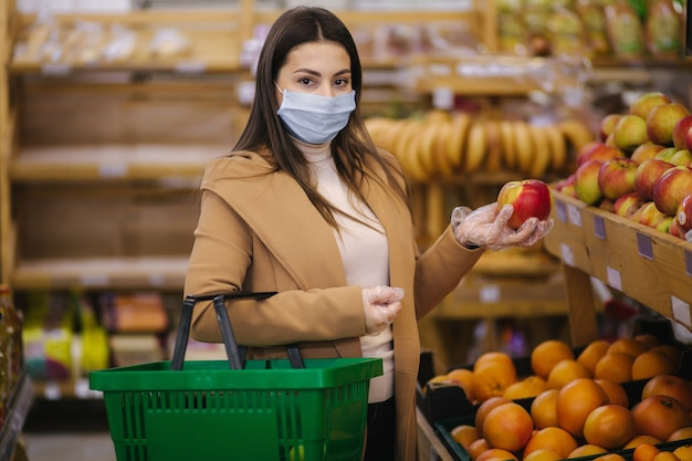 De jonge vrouw in beschermende handschoenen en gezichtsmasker houdt mooie verse appel in hand. mooi jong meisje met voedselmand die voedsel kiest door stand met fruit. winkelen tijdens quarantaine. covid-19 Premium Foto