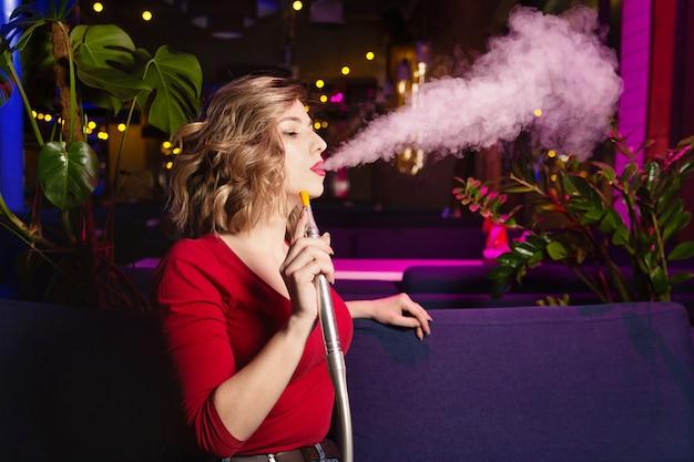De jonge vrouw in de rode kleding rookt een hookan. de nachtclub of bar rookt shisha. Premium Foto