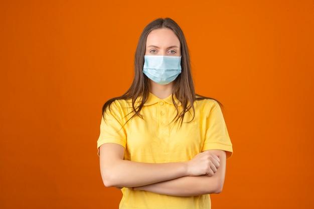 De jonge vrouw in geel poloshirt en medische beschermende maskerhanden kruiste op haar borst op oranje achtergrond Gratis Foto