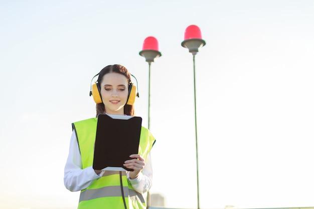 De jonge vrouw in het groene westen en de oorbeschermers bevinden zich op dak, greeptablet Premium Foto