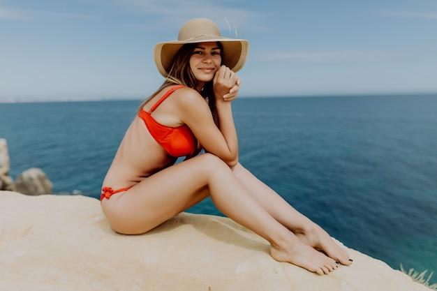 De jonge vrouw in rode bikini en strohoed, zittend op de rand van een heuvel met uitzicht op de oceaan Gratis Foto