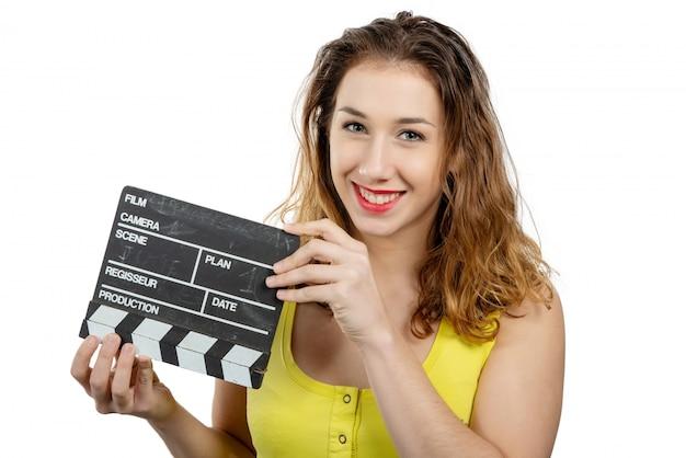 De jonge vrouw kleedde zich in geel met een filmklep op wit Premium Foto
