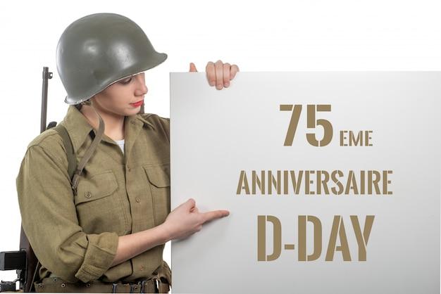 De jonge vrouw kleedde zich in ons wwii militair uniform met helm die uithangbord met d-dagverjaardag toont Premium Foto
