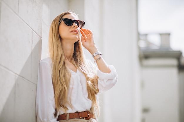 De jonge vrouw kleedde zich uit in de zomeruitrusting in de stad Gratis Foto