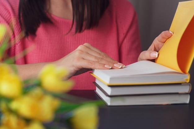 De jonge vrouw leest een boek thuis. onscherpe achtergrond. horizontaal, filmeffect. Premium Foto