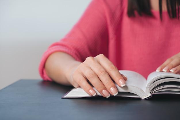 De jonge vrouw leest een boek thuis. Premium Foto