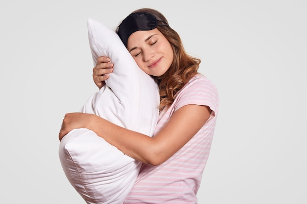De jonge vrouw leunt op hoofdkussen, draagt pyjama's en oogmasker, staat tegen wit, heeft slaperige uitdrukking Gratis Foto