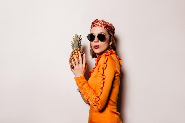 De jonge vrouw met rode lippen houdt ananas. portret van ondeugend meisje in oranje outfit en zonnebril op witte ruimte. Gratis Foto