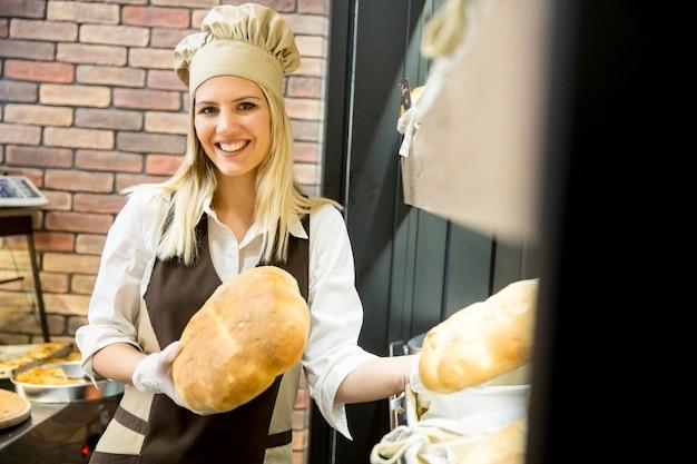 De jonge vrouw neemt vers brood van de planken in een bakkerswinkel Premium Foto