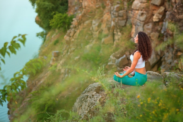 De jonge vrouw oefent yoga dichtbij rivier uit Gratis Foto