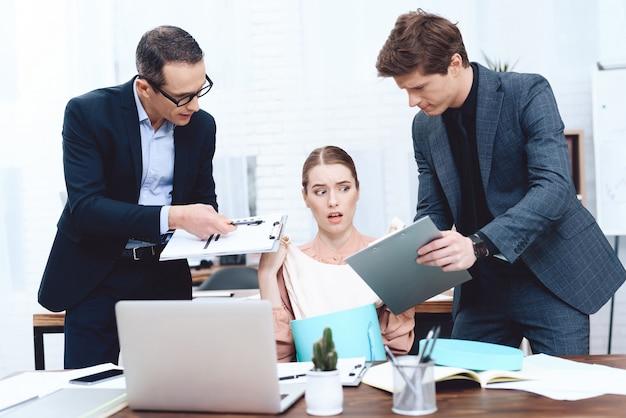 De jonge vrouw ontspant op het werk. leiders klagen erover. Premium Foto