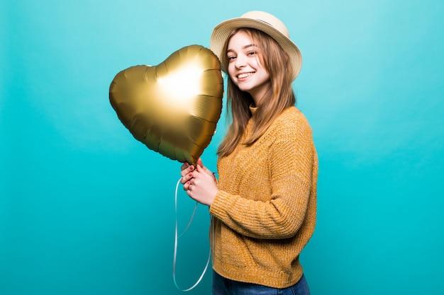 De jonge vrouw ontvangt lucht baloon op verjaardagsviering die over kleurenmuur wordt geïsoleerd Gratis Foto