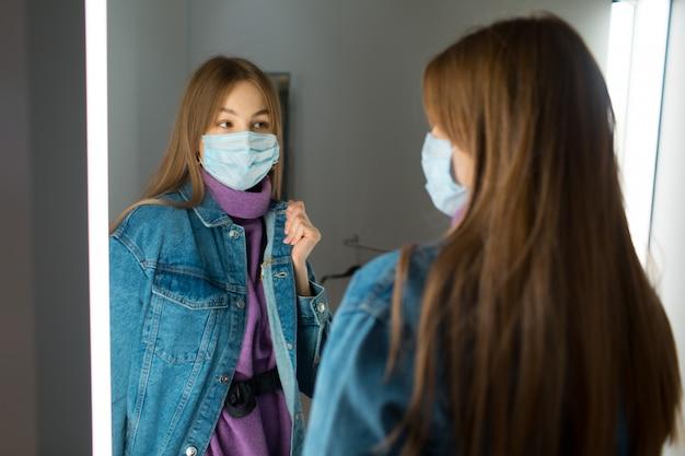 De jonge vrouw probeert kleren in kleedkamer met spiegel in winkel Premium Foto