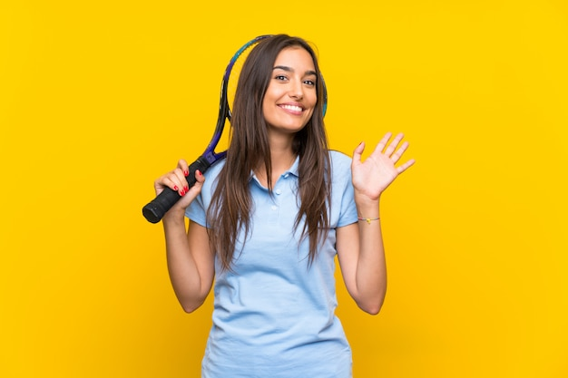 De jonge vrouw van de tennisspeler over het geïsoleerde gele muur groeten met hand met gelukkige uitdrukking Premium Foto
