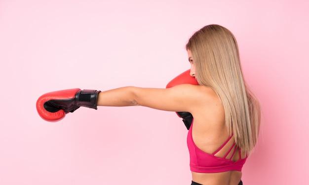 De jonge vrouw van het sportblonde met bokshandschoenen over geïsoleerd roze Premium Foto
