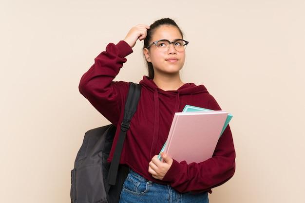 De jonge vrouw van het studenten aziatische meisje over geïsoleerde muur die twijfels hebben en met verwarren gezichtsuitdrukking Premium Foto