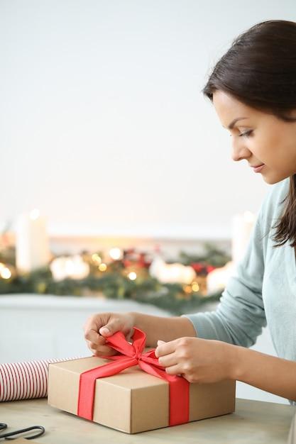 De jonge vrouw verpakkende kerstmis stelt voor Gratis Foto