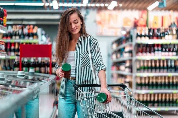 De jonge vrouw zet voedsel in een boodschappenwagentje in een supermarkt. klant kopen van producten in de supermarkt Premium Foto