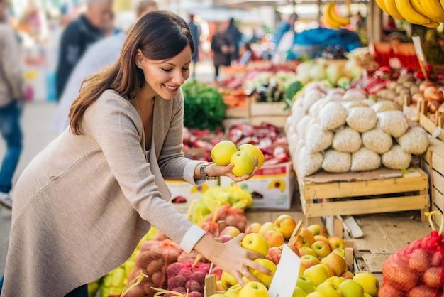 De jonge vrouw zoekt appelen bij groene markt. Premium Foto
