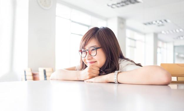 De jonge vrouwelijke student glimlacht met lege exemplaarruimte op bureau in bibliotheek in campus van universiteit Premium Foto