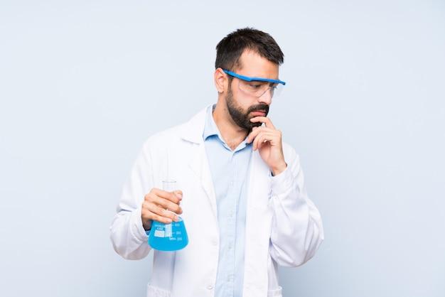De jonge wetenschappelijke fles van het holdingslaboratorium over geïsoleerde achtergrond die mond behandelen en aan de kant kijken Premium Foto
