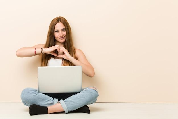 De jonge zitting van de gembervrouw op haar huisvloer die en een hartvorm met handen glimlacht toont. Premium Foto