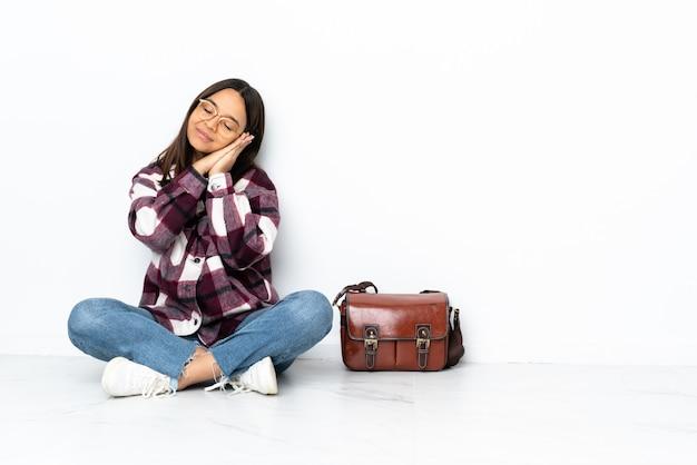 De jonge zitting van de studentenvrouw op de vloer die slaapgebaar in dorable uitdrukking maakt Premium Foto