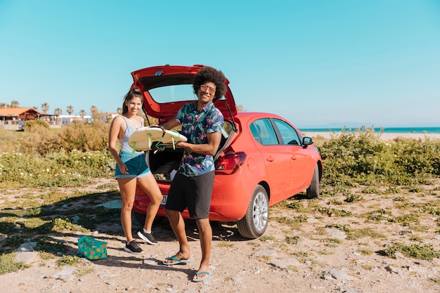 De jonge zwarte surfplank van de mensenholding dichtbij auto door kust Gratis Foto