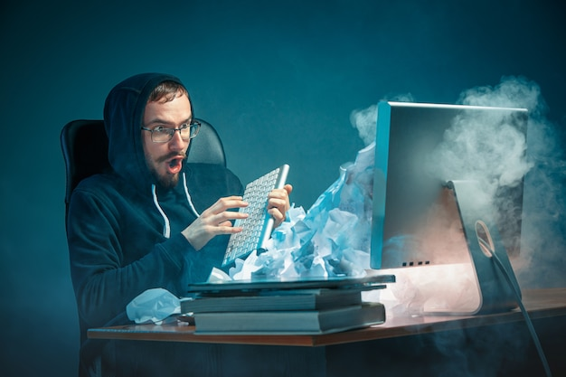 De jongelui beklemtoonde knappe zakenman die bij bureau in modern bureau werken die bij laptop het scherm schreeuwen en boos over spam zijn Gratis Foto