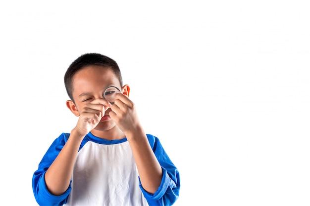 De jongen die iets ontdekt door een vergrootglas, business explore, searching, discovery en vision-concepten. Premium Foto