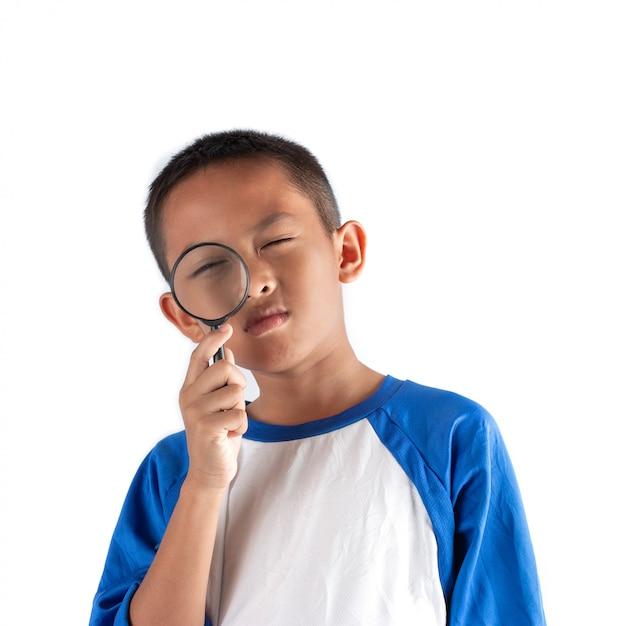 De jongen die iets ontdekt door een vergrootglas, business explore, searching, discovery en vision. Premium Foto