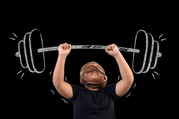 De jongen doet zich voor als een superheld en oefent door gewichten op te heffen. Gratis Foto