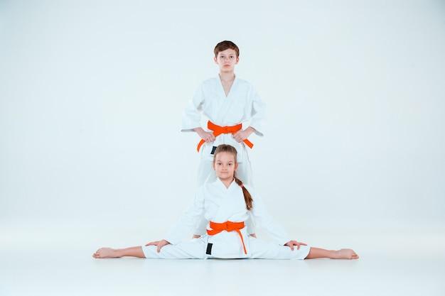 De jongen en het meisje poseren op aikido training in martial arts school. gezonde levensstijl en sport concept Gratis Foto