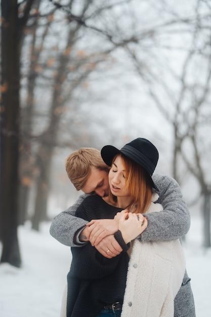 De jongen en het meisje rusten in het winterbos. Gratis Foto