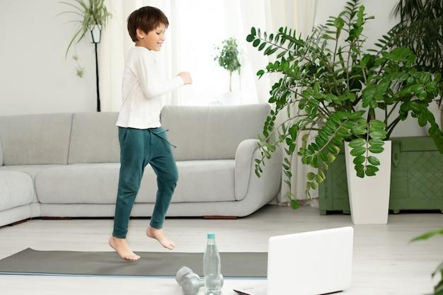De jongen gaat thuis online sporten. het kind doet oefeningen in de kamer. Premium Foto