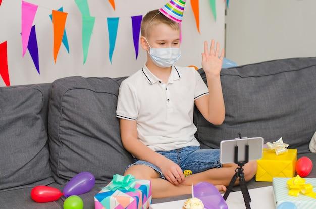 De jongen in geneeskunde gezichtsmasker viert verjaardag door videogesprek aan telefoon Premium Foto