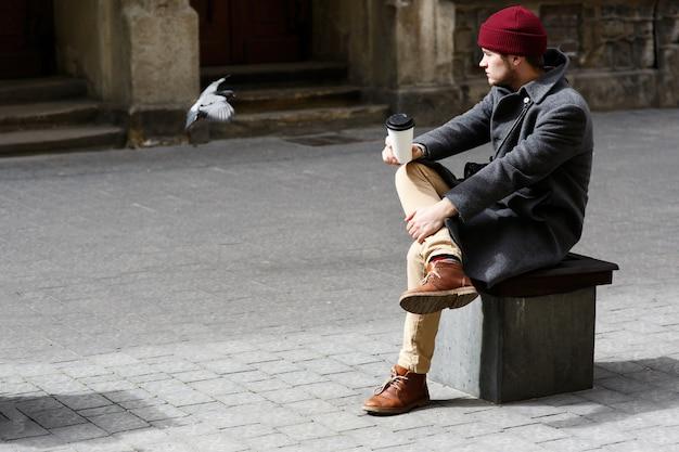 De jongen in rode hoed bekijkt duif vliegend rond hem Gratis Foto