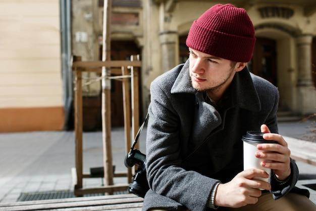 De jongen in rode hoed met camera op zijn schouder zit op de straat Gratis Foto