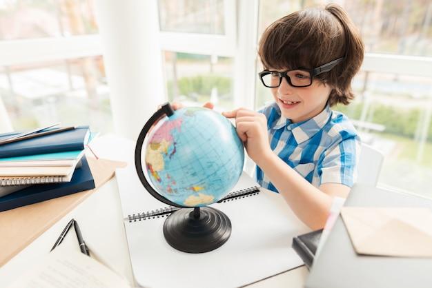 De jongen kijkt thuis naar de wereld. Premium Foto
