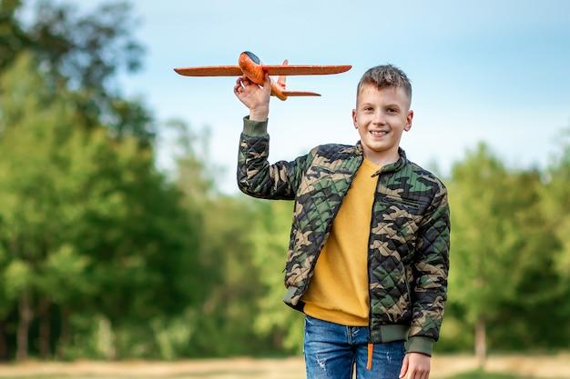 De jongen lanceert een speelgoedvliegtuig. Premium Foto
