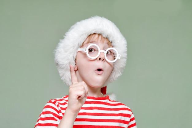 De jongen met een bril en een kerstmuts dreigt met zijn vinger. portret Premium Foto
