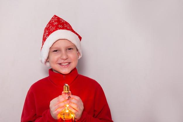 De jongen met een nieuwjaarsmuts met een magische lamp Premium Foto