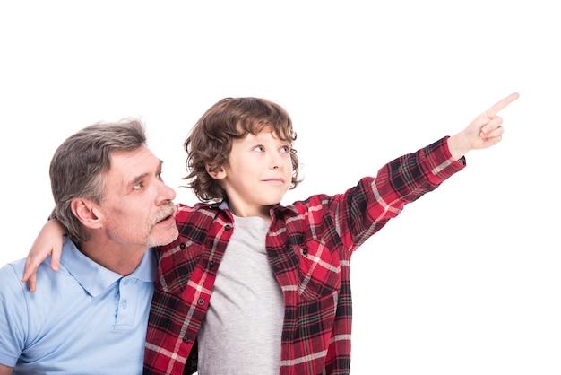De jongen met zijn opa, wijst ergens met de hand. Premium Foto