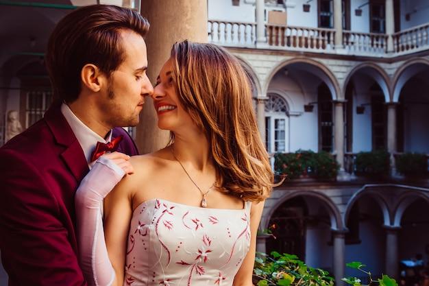 De jongen omhelst zijn vriendin tussen verschillende schilderijen en architectuur Premium Foto