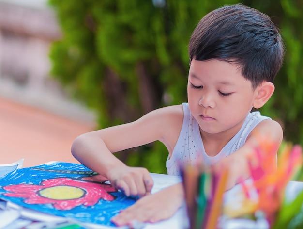 De jongen schildert kleurrijk beeld thuis. Gratis Foto