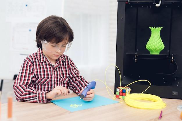 De jongen schrijft door 3d pen tijdens een les in klasse. Premium Foto